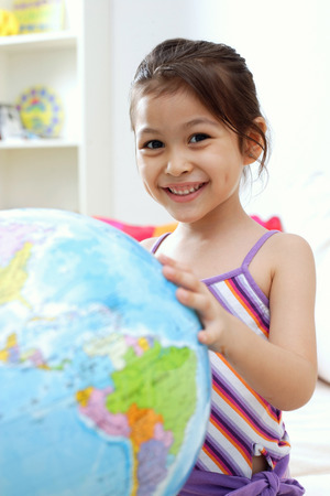 Young girl touching globe, looking at camera, smiling