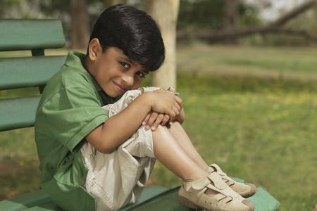 hugging knees: Little boy hugging knees on park bench LANG_EVOIMAGES