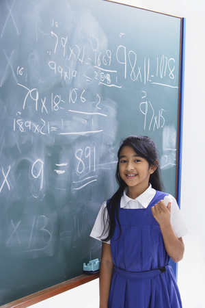 sums: girl in front of chalkboard smiling