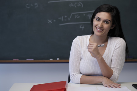 Young teacher sitting at desk in front of chalkboard and smiling