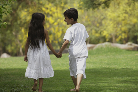 two children holding hands walking