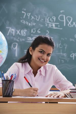 librarians: teacher at desk, smiling at camera (vertical)