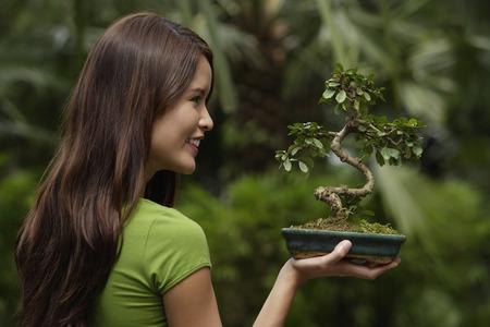 Profile of young woman holding bonsai tree