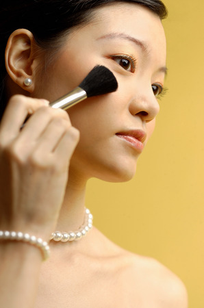 Woman putting on blusher with make up brush