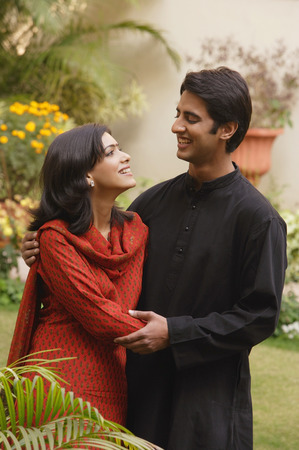 husband and wife in garden embracing, smiling at each other Stock Photo