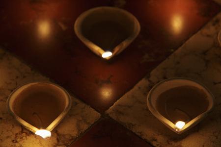 Lit clay oil lamps on floor