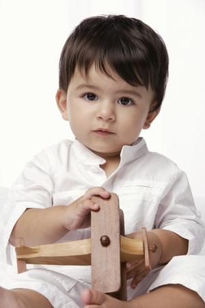 baby boy holding toy airplane Stock Photo