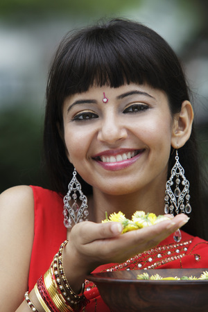 Head shot of Indian woman smiling and holding flowers