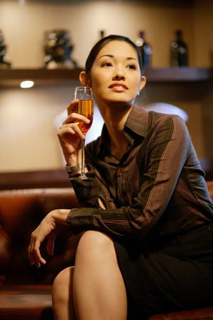 Woman with champagne glass, legs crossed, looking away