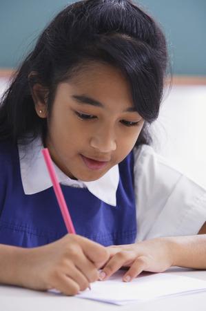 girl concentrates on schoolwork Banco de Imagens