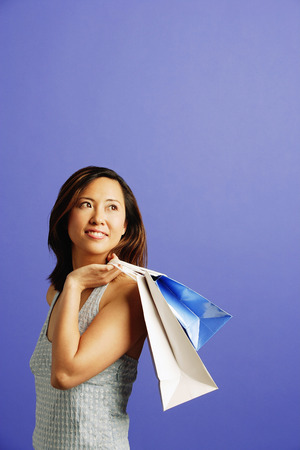 over the shoulder: Woman carrying shopping bags over shoulder, looking away