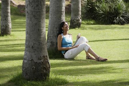 teen girl listening to music in park