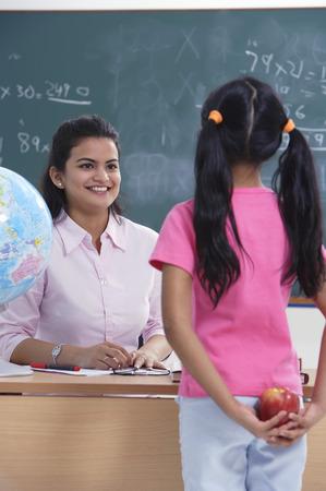 librarians: student holding apple for teacher LANG_EVOIMAGES