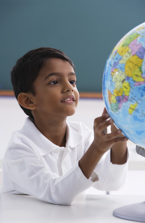 world at your fingertips: young boy looks at globe, hands touching
