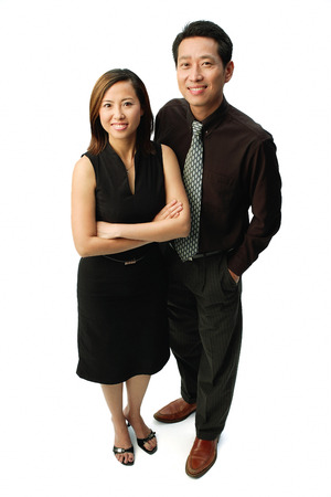 Couple standing, smiling at camera, woman with arms crossed
