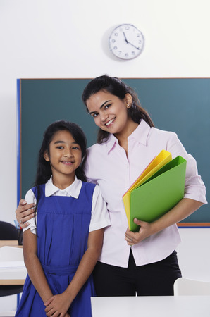 librarians: teacher with arm around student, both smile at camera