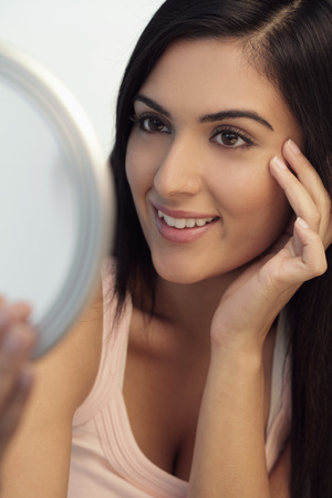 indian subcontinent ethnicity: Young woman looking at mirror smiling while touching her face LANG_EVOIMAGES