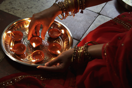 indian subcontinent ethnicity: Close up of woman wearing a sari, putting oil lamps on silver tray