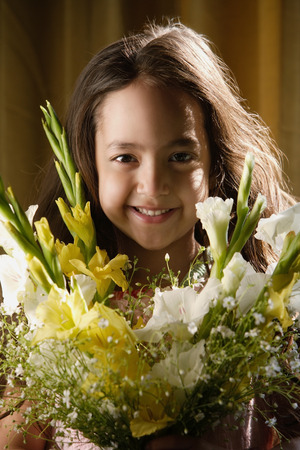 little girl smiling over bouquet of flowers LANG_EVOIMAGES