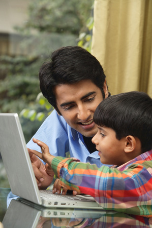 father and son work at laptop Stock Photo