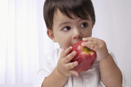 baby boy eating apple LANG_EVOIMAGES