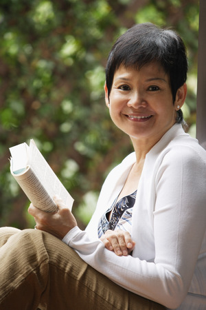 Woman relaxing with book in the garden and smiling at camera