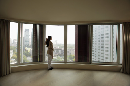 think through: Young woman looking out large windows of condo
