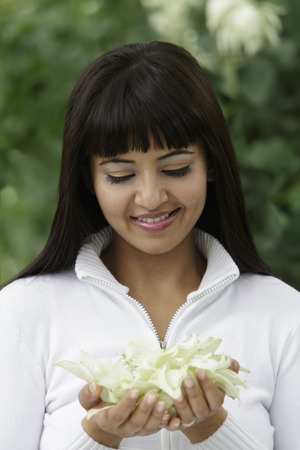 Head shot of woman looking at flowers in her hands