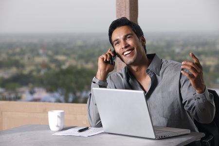 man on phone, working at laptop computer