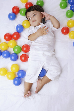 european ethnicity: baby boy surrounded by balls, cell phone to ear LANG_EVOIMAGES