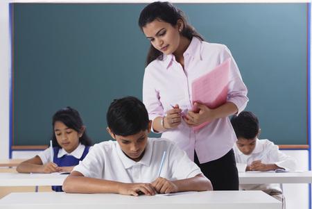 librarians: teacher overlooking schoolwork
