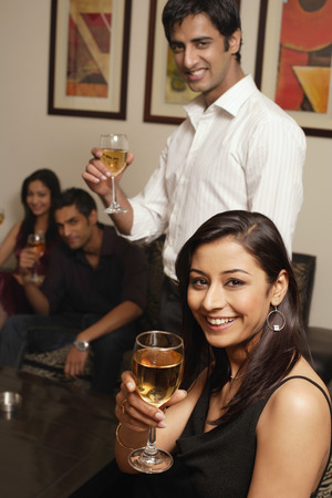 couple at party facing camera, glasses raised