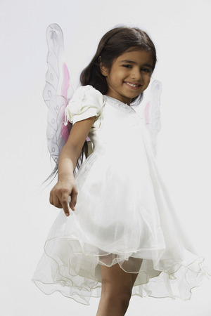 little girl dressed in white dress and wings