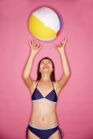 tossing: Young woman in bikini, tossing beach ball