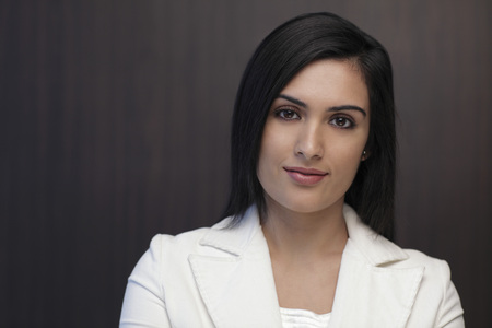 indian subcontinent ethnicity: Head shot of young woman wearing suit and smiling