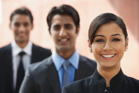 accommodating: smiling businesswoman, two businessman in background