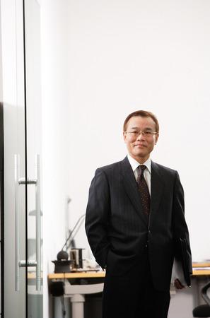 mature business man: Businessman standing, looking at camera, portrait LANG_EVOIMAGES