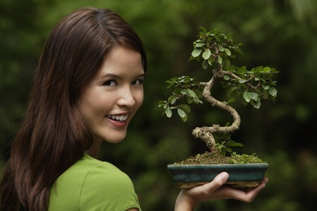 Young woman holding up bonsai tree