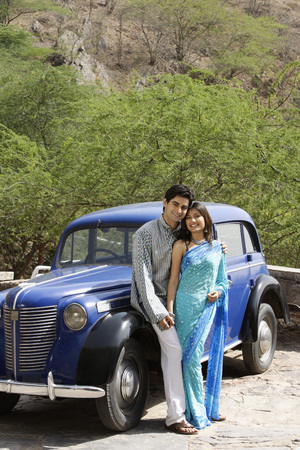 kurta: young couple standing in front of blue antique car LANG_EVOIMAGES