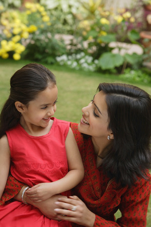 mother and daughter in garden, embracing, smiling at each other Stock Photo
