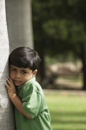 Little boy hugging tree trunk
