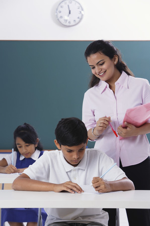 librarians: two students at desk, teacher standing LANG_EVOIMAGES