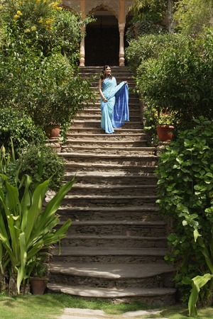 body built: young woman in sari, standing on stairs