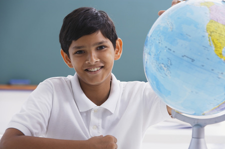 world at your fingertips: boy smiles at camera with globe