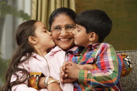 grandkids kiss grandmother cheeks