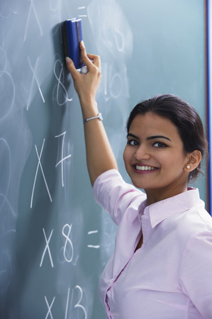 librarians: teacher smiling as she erases at chalkboard