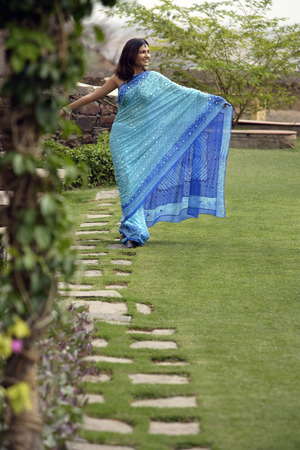 stretch out: young woman wearing sari walking in garden, arms stretch out LANG_EVOIMAGES