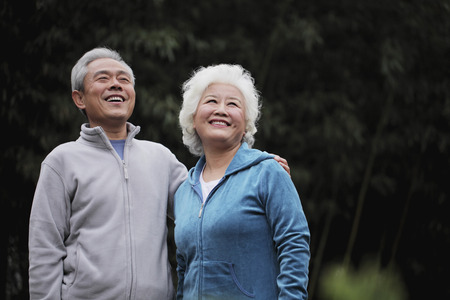 A senior couple looking up and smiling