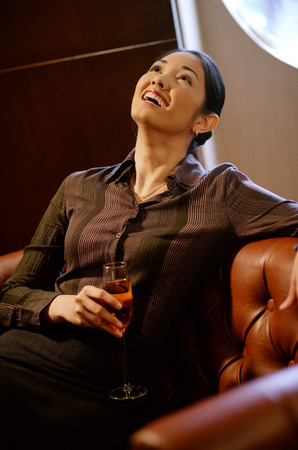 Woman with champagne glass, looking up, smiling Stock Photo