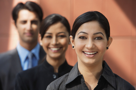 two businesswomen smiling at camera, one businessman (first woman in focus) Stok Fotoğraf